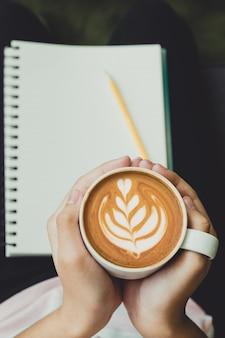Ciérrese encima de la mano que sostiene la taza de café caliente del capuchino con arte del latte del corazón en la tienda del café, pasatiempo