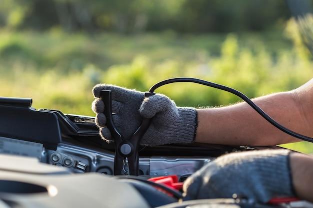 Ciérrese encima de la mano del técnico del coche que sostiene el cable para conectar con la batería