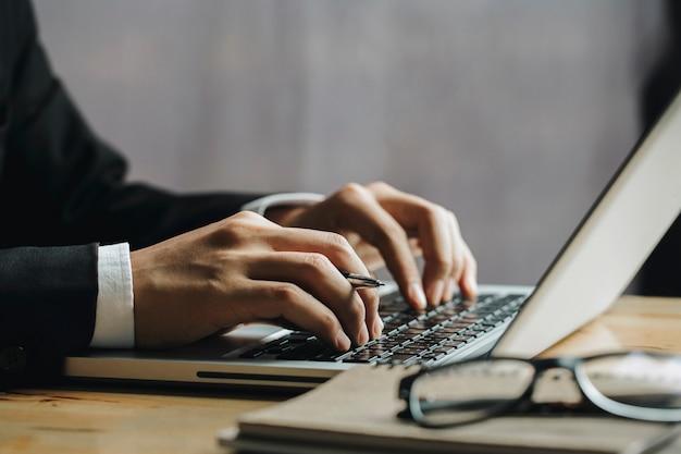 Ciérrese encima de las manos del hombre de negocios usando la computadora portátil. concepto financiero