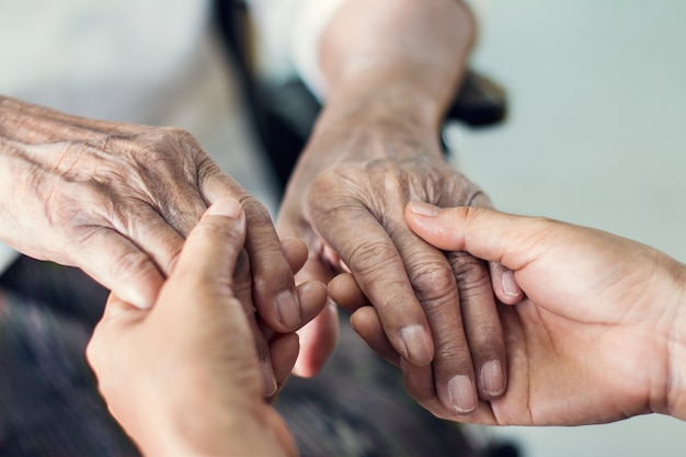 Ciérrese encima de las manos de las manos amigas cuidado casero mayor.