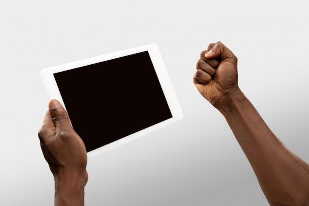 Ciérrese encima de las manos masculinas que sostienen la tableta con la pantalla en blanco durante la observación en línea de partidos deportivos populares y campeonatos en todo el mundo.
