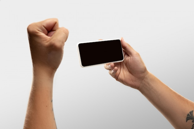Ciérrese encima de las manos masculinas que sostienen el teléfono con la pantalla en blanco durante la observación en línea de partidos y campeonatos deportivos populares en todo el mundo.