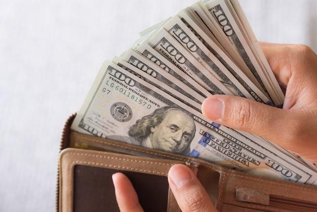 Ciérrese encima de las manos de la mujer que sacan el dinero billetes de banco de los dólares de américa de la cartera.