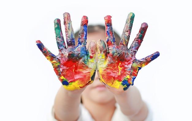 Ciérrese encima de las manos del niño pintadas en las pinturas coloridas aisladas.