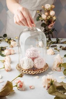 Ciérrese encima de las manos recortadas ama de casa femenina chef cocinero pastelero o panadero en delantal camiseta blanca empaquetado pastel zephyr en la mesa.