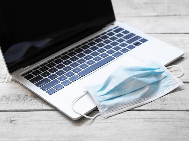 Ciérrese encima de la máscara blanca y del cuaderno del ordenador en el vintage blanco de madera con el espacio de la copia.