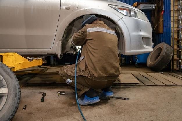 Ciérrese encima del mecánico de automóviles profesional que cambia la rueda de coche en servicio de reparación auto. trabajador automático haciendo reemplazo de neumáticos o ruedas en el garaje de la estación de servicio de reparación