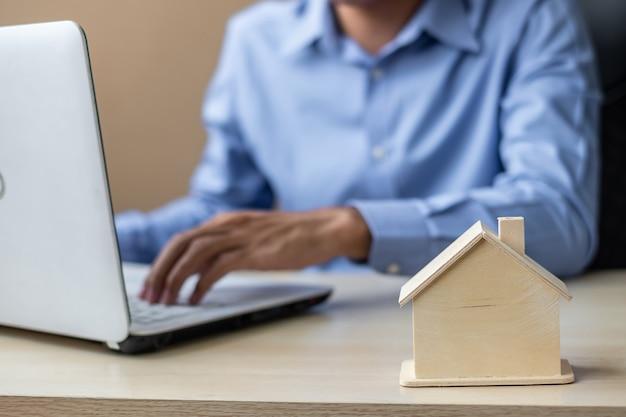 Ciérrese encima de modelo de madera de la casa, hombre de negocios usando el ordenador portátil.