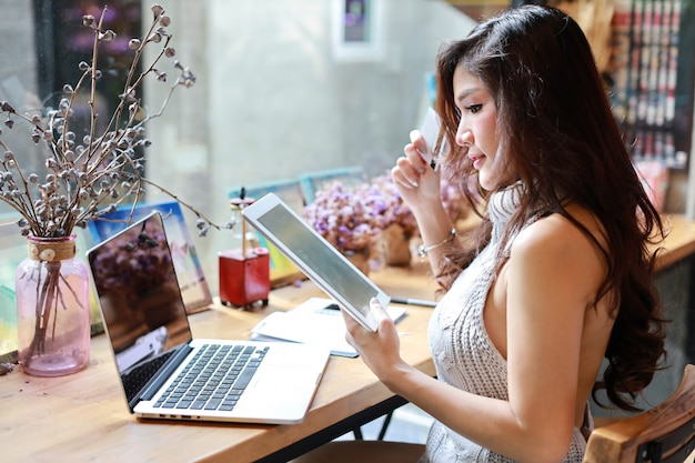 Ciérrese encima de la mujer asiática hermosa y atractiva, pelo largo en la ropa informal gris que trabaja en la tableta