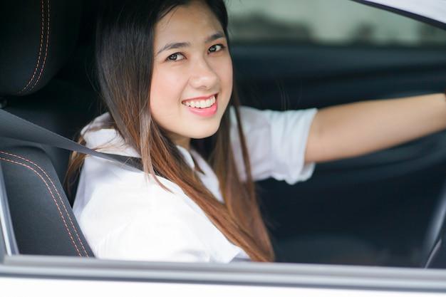 Ciérrese encima de la mujer asiática que conduce en el coche e intente parquear, concepto de trabajo de la mujer de negocios.