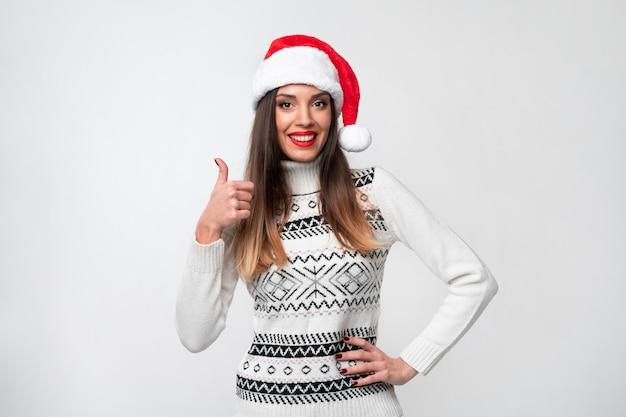 Ciérrese encima de la mujer caucásica beautifiul del retrato en el sombrero rojo de papá noel en la pared blanca. concepto de navidad año nuevo. linda mujer dientes sonriendo emociones positivas mostrando los pulgares para arriba