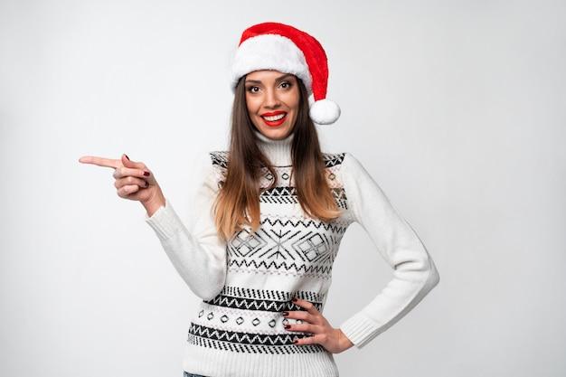 Ciérrese encima de la mujer caucásica beautifiul del retrato en el sombrero rojo de papá noel en la pared blanca. concepto de navidad año nuevo. linda mujer dientes sonriendo positivo mostrando el dedo índice lado