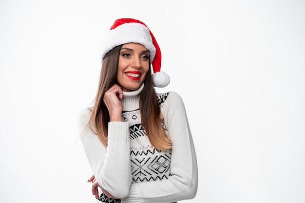 Ciérrese encima de la mujer caucásica beautifiul del retrato en el sombrero rojo de papá noel en la pared blanca. concepto de navidad año nuevo. linda mujer mano en dientes de collar sonriendo emociones positivas con espacio libre