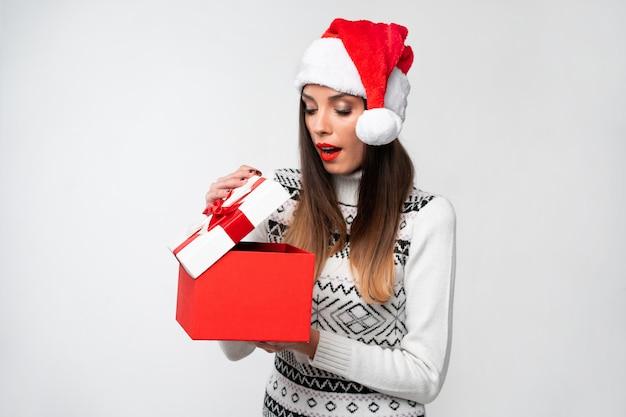 Ciérrese encima de la mujer caucásica beautifiul del retrato en el sombrero rojo de papá noel en la pared blanca. concepto de navidad año nuevo sorprendido linda mujer dientes sonriendo emociones positivas abren gran caja de regalo roja