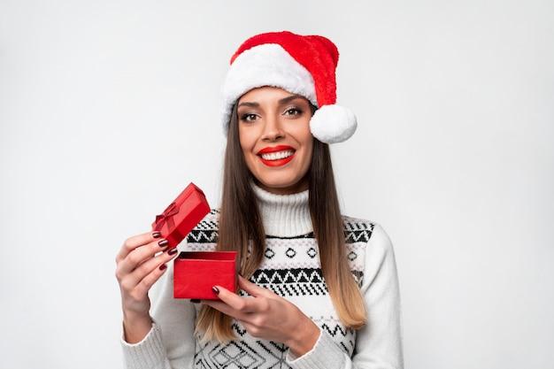 Ciérrese encima de la mujer caucásica beautifiul del retrato en el sombrero rojo de papá noel en la pared blanca. concepto de navidad año nuevo sorprendido linda mujer dientes sonriendo emociones positivas abren pequeña caja de regalo roja