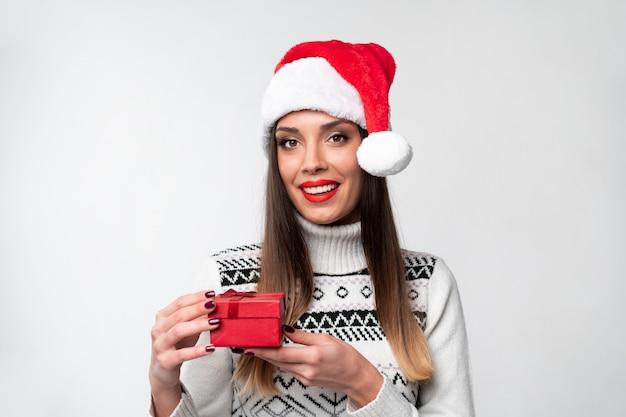 Ciérrese encima de la mujer caucásica beautifiul del retrato en el sombrero rojo de papá noel en la pared blanca. concepto de navidad año nuevo sorprendido linda mujer dientes sonriendo emociones positivas con pequeña caja de regalo roja
