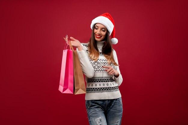 Ciérrese encima de la mujer caucásica beautifiul del retrato en el sombrero rojo de santa en la pared roja. concepto de navidad año nuevo. dientes de mujer linda sonriendo emociones positivas con bolsa de compras.