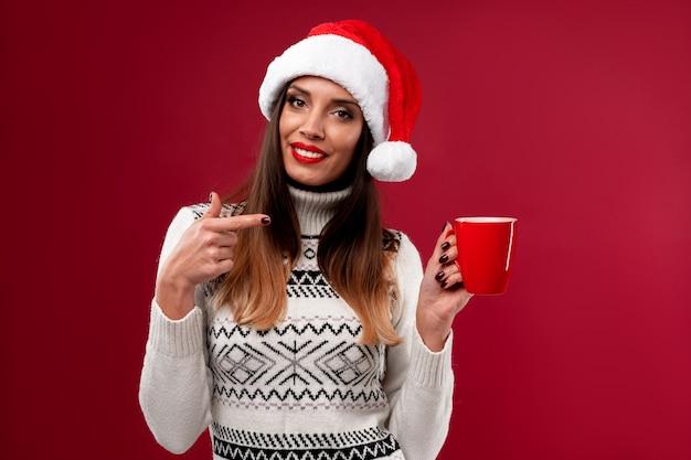 Ciérrese encima de la mujer caucásica beautifiul del retrato en el sombrero rojo de santa en la pared roja. concepto de navidad año nuevo. linda mujer dientes sonriendo emociones positivas con rojo taza de café en las manos