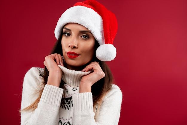 Ciérrese encima de la mujer caucásica beautifiul del retrato en el sombrero rojo de santa en la pared roja. concepto de navidad año nuevo. linda mujer mano en dientes de collar sonriendo emociones positivas con espacio libre