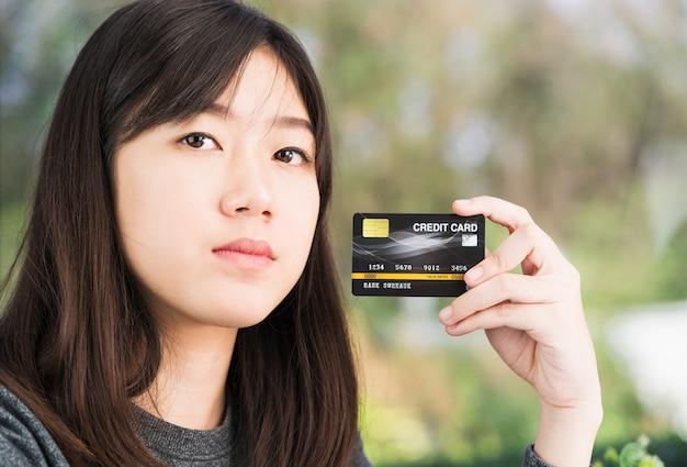 Ciérrese encima de la mujer joven que sostiene la tarjeta de crédito