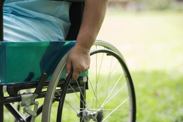 Ciérrese encima de la mujer mayor sola que se sienta en la silla de ruedas en el jardín en hospital