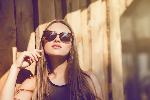 Ciérrese encima de mujer de la moda del retrato en gafas de sol