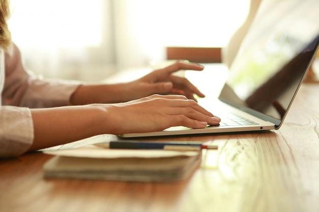 Ciérrese encima de la mujer de negocios que escribe en la computadora portátil en el escritorio de madera