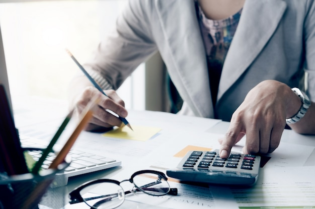 Ciérrese encima de la mujer de negocios que usa la calculadora y la computadora portátil para las finanzas de las matemáticas