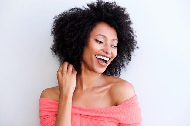 Ciérrese encima de la mujer negra joven atractiva que ríe contra el fondo blanco