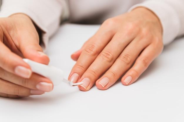 Ciérrese encima de la mujer que barniza las uñas en casa. auto fortalecimiento de uñas mientras está en cuarentena
