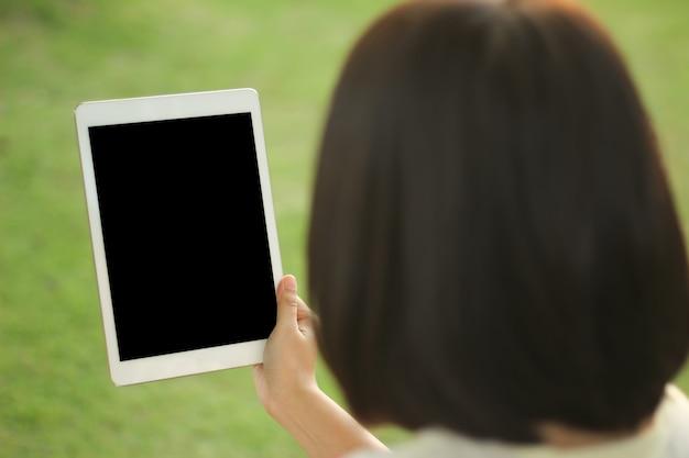 Ciérrese encima de la mujer que sostiene y que usa la tableta mientras que se sienta en al aire libre, trabajando en parque