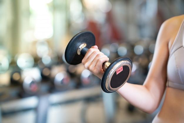 Ciérrese encima de mujeres con pesas en manos el gimnasio