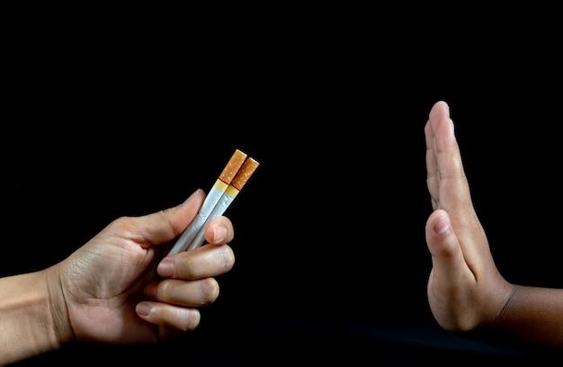 Ciérrese encima de oferta del cigarrillo del rechazo de la mano del hombre en fondo negro.