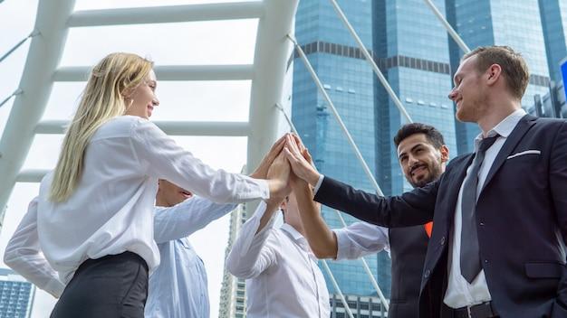 Ciérrese encima de la opinión los hombres de negocios jovenes que ponen sus manos juntas. unidad y trabajo en equipo.
