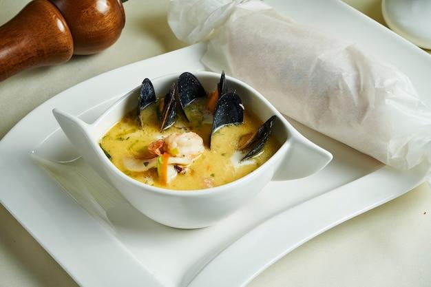 Ciérrese encima de la opinión sobre la sopa casera fresca de waterzooi - plato de guisado de bélgica. crema amarilla mejillón y camarones en un tazón blanco. comida del restaurante