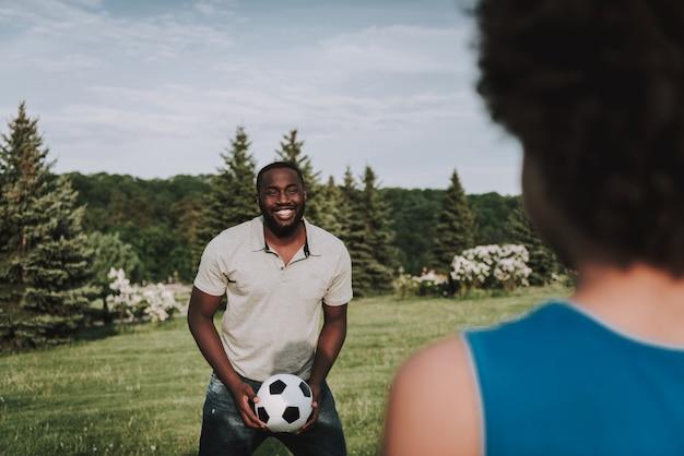 Ciérrese encima de papá que sostiene la bola y párese enfrente del hijo.