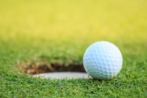 Ciérrese encima de la pelota de golf en el labio de la taza en curso