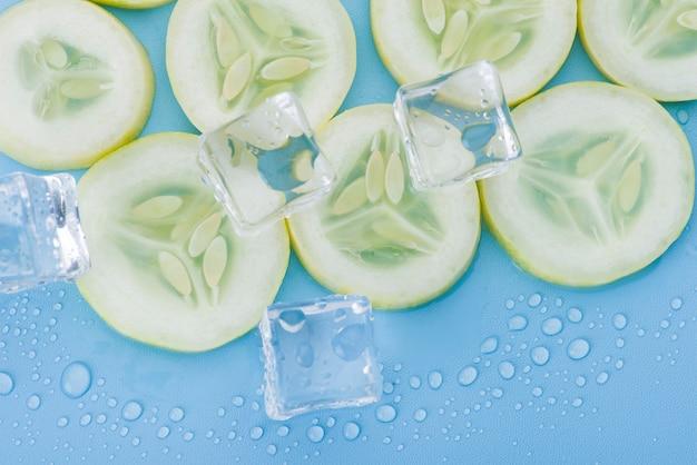 Ciérrese encima del pepino fresco de la rebanada con el cubo de hielo en azul