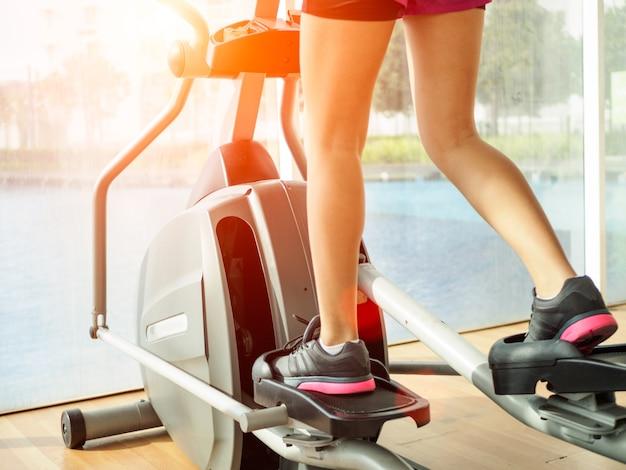 Ciérrese encima de las piernas de la mujer que se resuelven en la bicicleta estática en gimnasio de la aptitud.