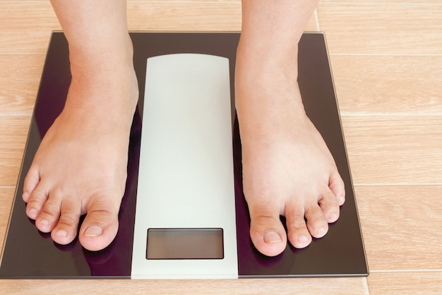 Ciérrese encima de los pies femeninos que se colocan en escala del peso con el espacio de la copia.