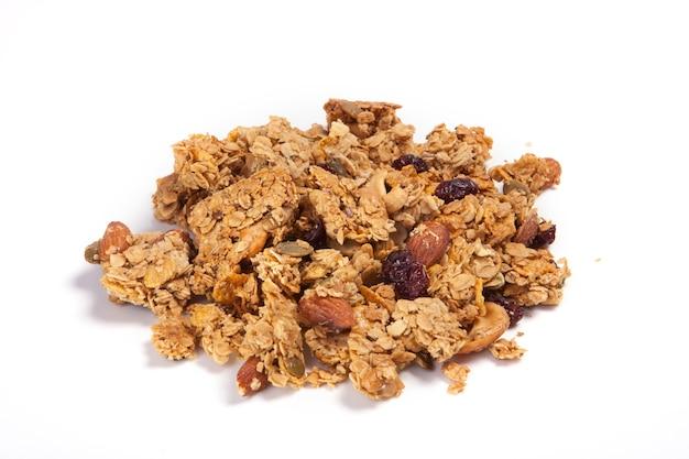 Ciérrese encima de pila granola aislada en el fondo blanco.