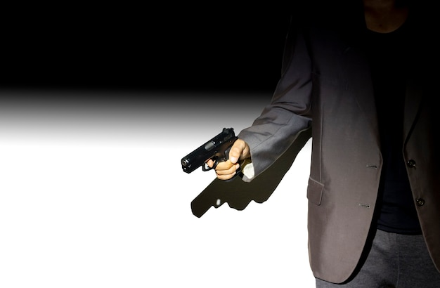 Ciérrese encima del pistolero en fondo oscuro