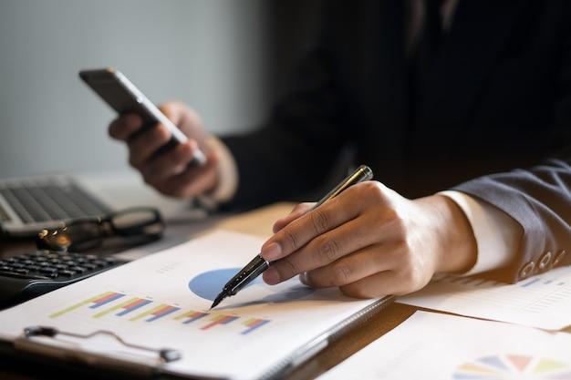 Ciérrese encima de pluma de tenencia de la mano del hombre de negocios y señalar en el papeleo financiero con el teléfono celular.