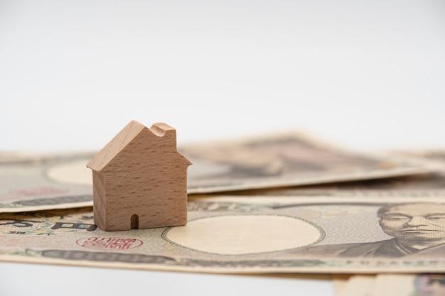 Ciérrese encima de poca casa de madera en billete de banco japonés del dinero de los yenes de la moneda. japón economía de la industria de bienes raíces.