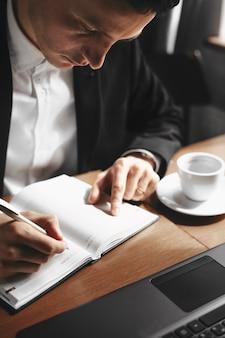 Ciérrese encima del retrato de un administrador adulto que toma notas mientras bebe una taza de café.