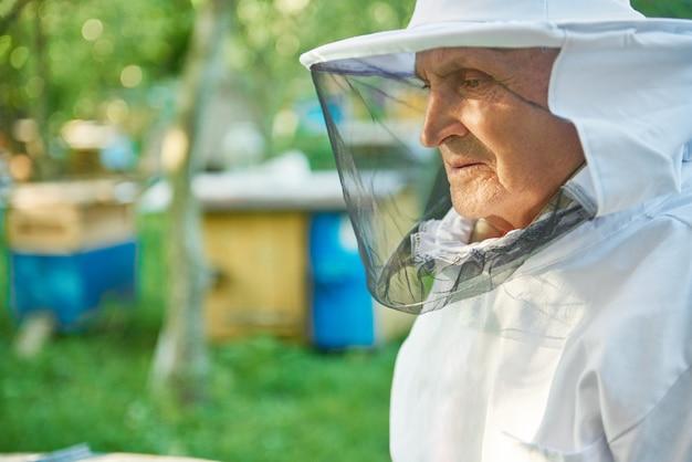 Ciérrese encima del retrato de un apicultor mayor que lleva el traje de la apicultura que mira lejos el copyspace jubilado antigüedad jubilado profesión profesión hobby estilo de vida agricultor campo retiro