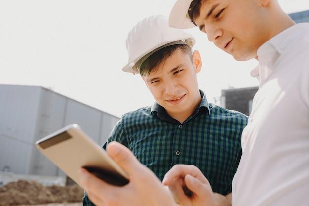 Ciérrese encima del retrato del arhitect joven que escucha a su dueño dónde comenzar a trabajar en el edificio.