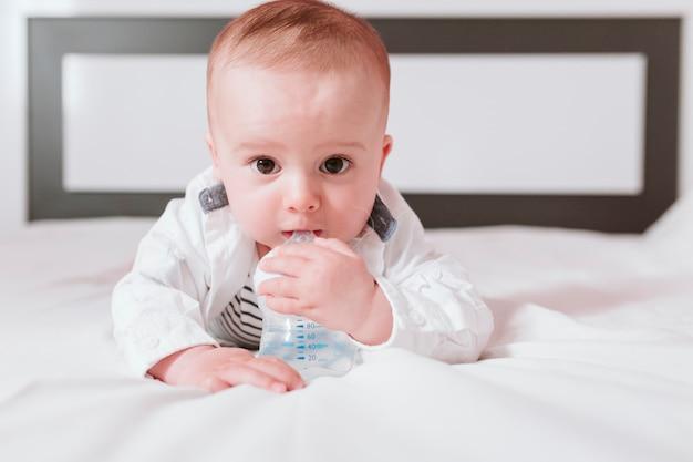 Ciérrese encima del retrato del bebé en la cama que sostiene el biberón