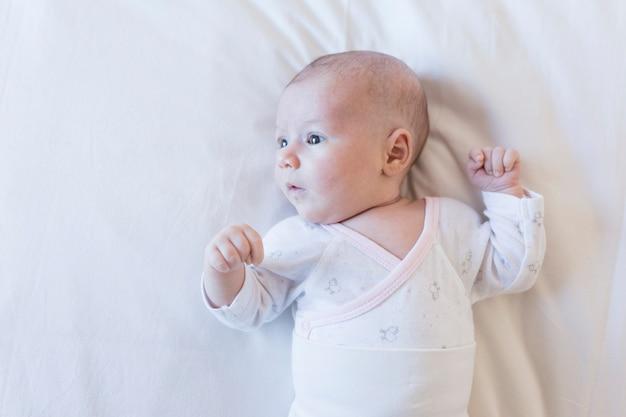 Ciérrese encima del retrato de un bebé hermoso en el fondo blanco en casa