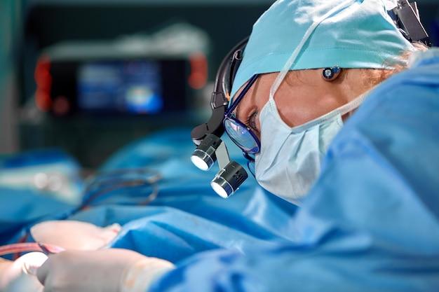 Ciérrese encima del retrato del doctor de sexo femenino del cirujano que lleva la máscara protectora y el sombrero durante la operación. salud, educación médica, concepto de cirugía.